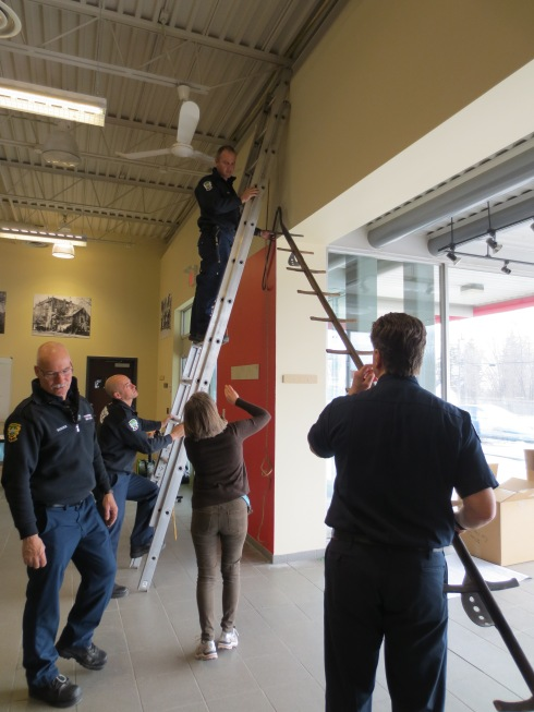 Q: How many firefighters does it take to hang up a historic ladder?